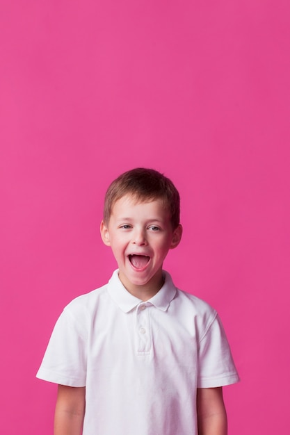 Tittle boy standing near pink wall with mouth open Free Photo