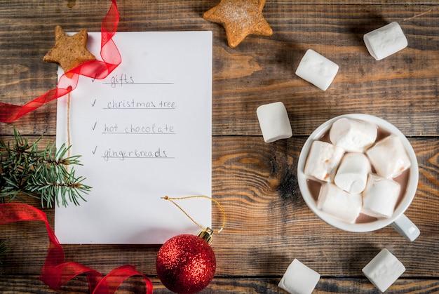 クリスマス、新年のコンセプト。木製のテーブル、to doリスト付きのノート(ジンジャーブレッド、ギフト、ホットチョコレート、クリスマスツリー Premium写真
