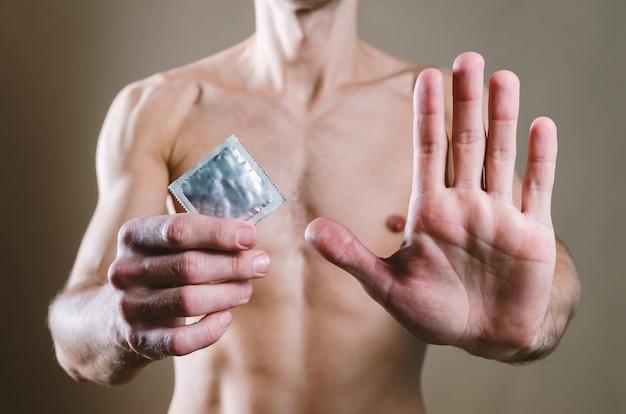 腰にはブラックジーンズを着た魅力的な裸の男性がコンドームを持っており、もう一方の手は開いた手です Premium写真