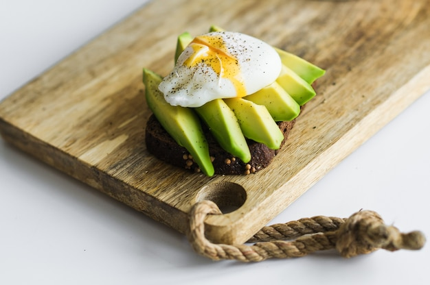 Toast, avacado sandwich and poached egg on a wooden chopping board. Premium Photo