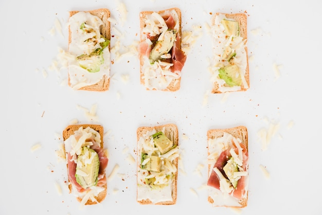 Toast bread with grated cheese; ham and avocado slice on white backdrop Free Photo