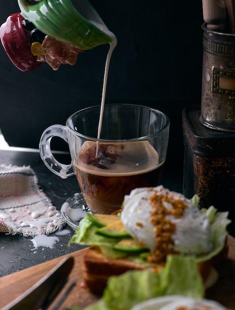 Тост хлеб с нарезанный авокадо, посыпать яйцом и зеленью на деревянной разделочной доске. Premium Фотографии