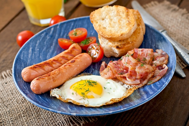 Toast, egg, bacon and vegetables in a rustic style on wooden surface Free Photo