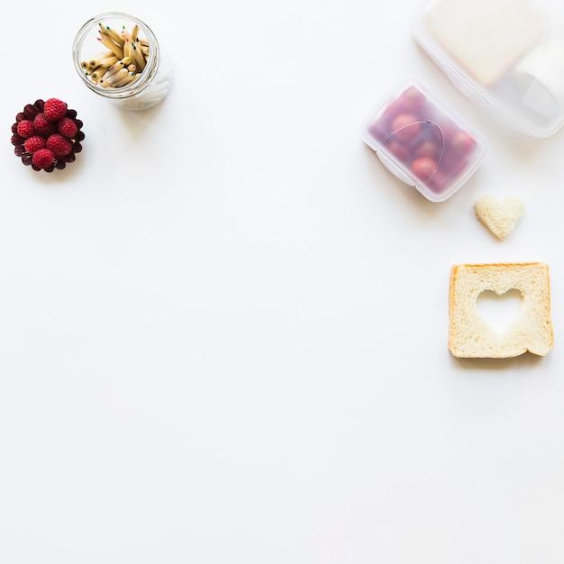 Toast and pencils near healthy food Free Photo