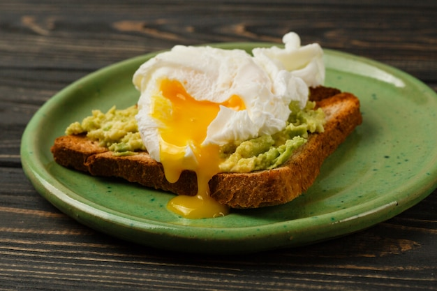 Toast and poached egg with avocado on a green plate on wooden table Premium Photo