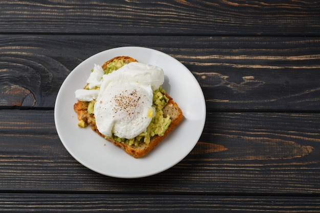 Toast and poached egg with avocado on a plate on wooden table Premium Photo