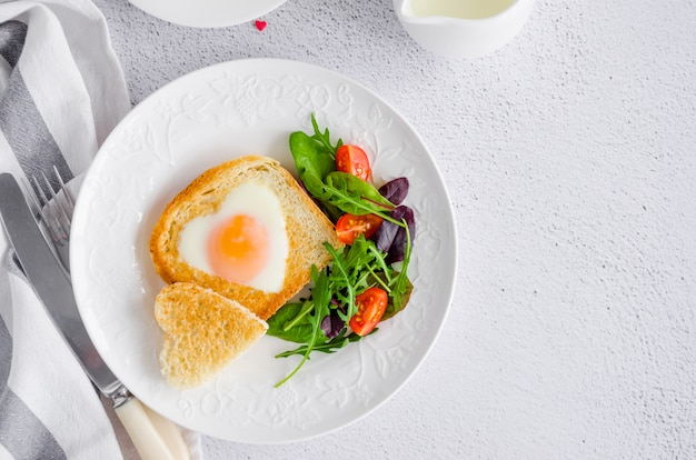Toast in shape of heart with egg on a white plate with arugula and cherry tomatoes Premium Photo
