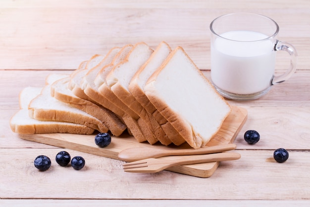 Toast wheat bread sliced and cow milk on wooden Premium Photo