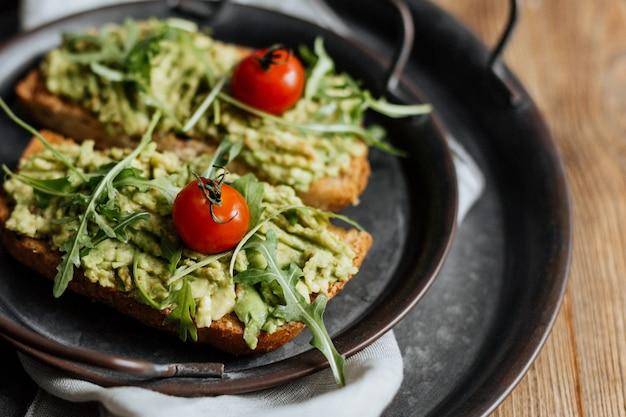 アボカド、ルッコラ、チェリートマトのトーストを鉄板でお召し上がりください。 Premium写真