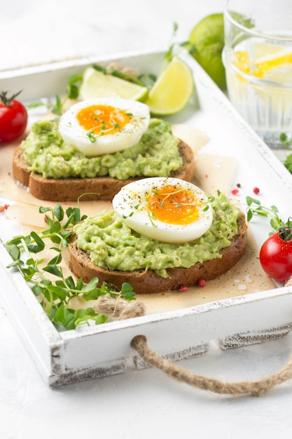 Toast with avocado puree and soft-boiled egg on white tray, liquid yolk, delicious breakfast, light sandwich Premium Photo