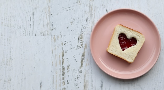 Toast with heart-shaped jam on a pink plate, wooden white table flat lay Premium Photo