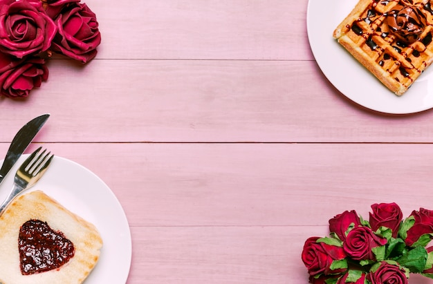 Toast with jam in heart shape with belgian waffle and roses Free Photo