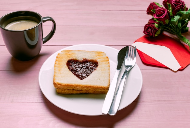 Toast with jam in heart shape with roses and coffee Free Photo