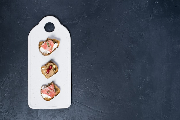 Toast with parma, salami and goose pate on a white chopping board Premium Photo
