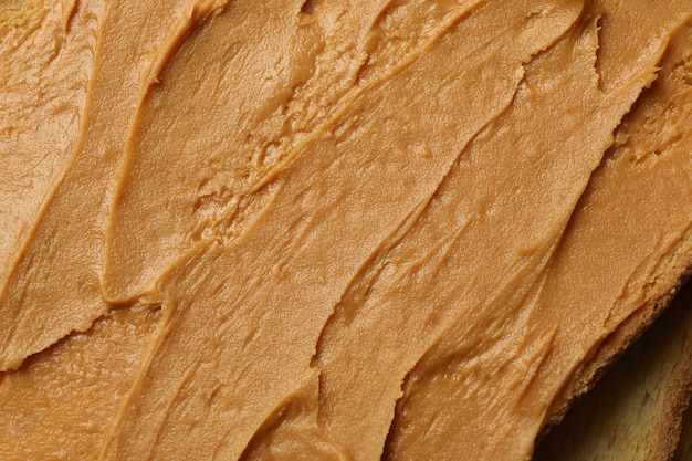 Toast with peanut butter on whole background close up Premium Photo