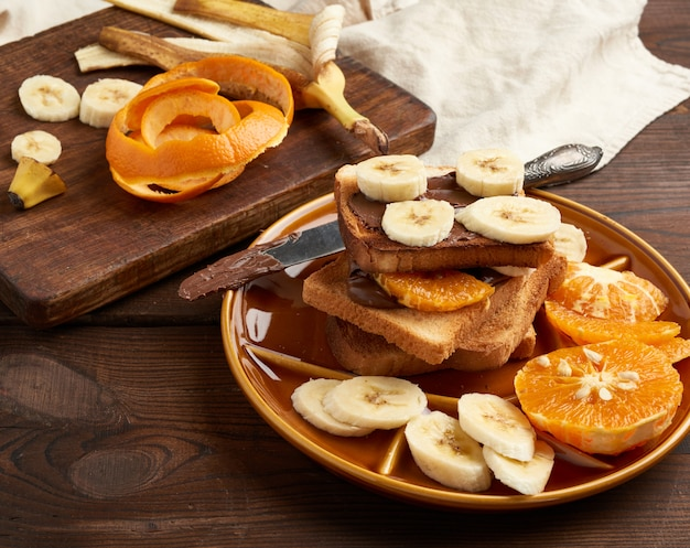 Toasted sandwiches with chocolate paste and banana slices on a plate, morning breakfast Premium Photo
