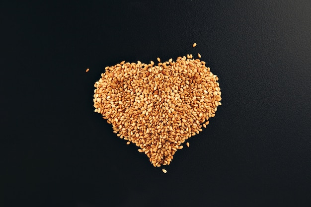 Toasted white sesame seeds arranged in a shape of heart on a smooth black table surface Free Photo