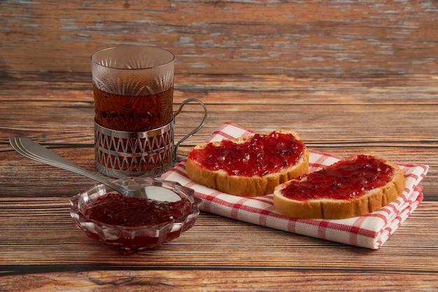 Тосты со сливовым конфитюром и стаканом чая. Бесплатные Фотографии