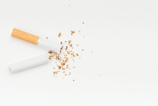 Tobacco coming from broke cigarette against white backdrop Free Photo