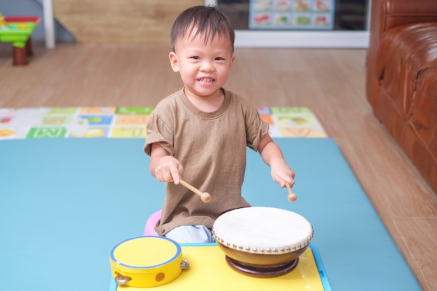 Toddler baby boy child hold sticks & plays a musical instrument drum in play room at home Premium Photo