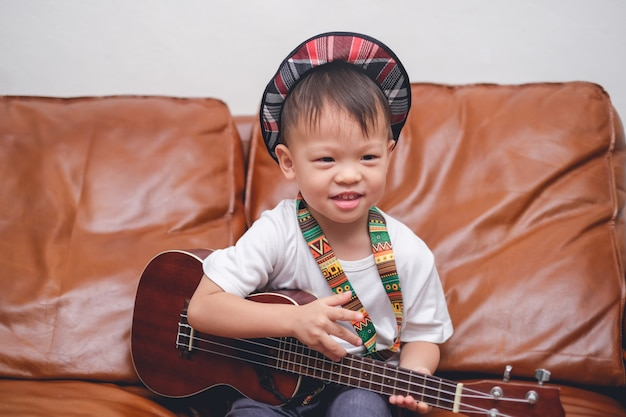 Toddler baby boy child wearing hat hold & play hawaiian guitar or ukulele in living room Premium Photo