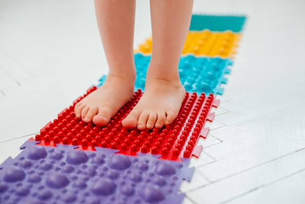 Toddler on baby foot massage mat. exercises for legs on orthopedic massage carpet. prevention of flat feet and hallux valgus Premium Photo