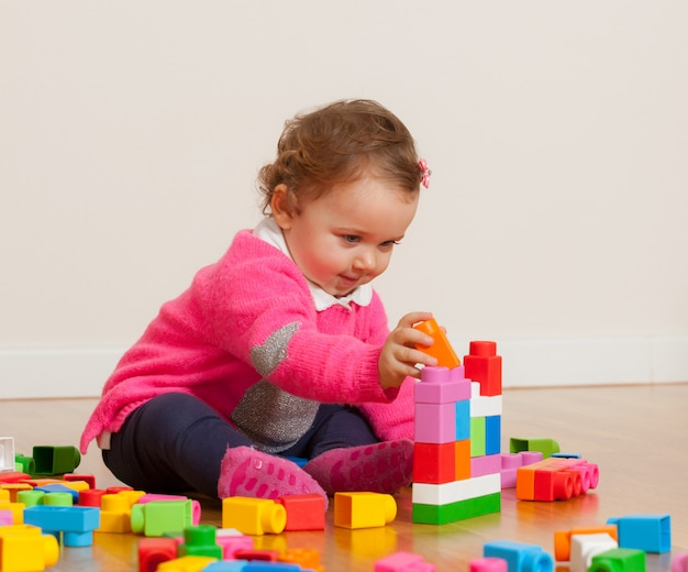 Toddler baby girl playing with rubber building blocks. Premium Photo