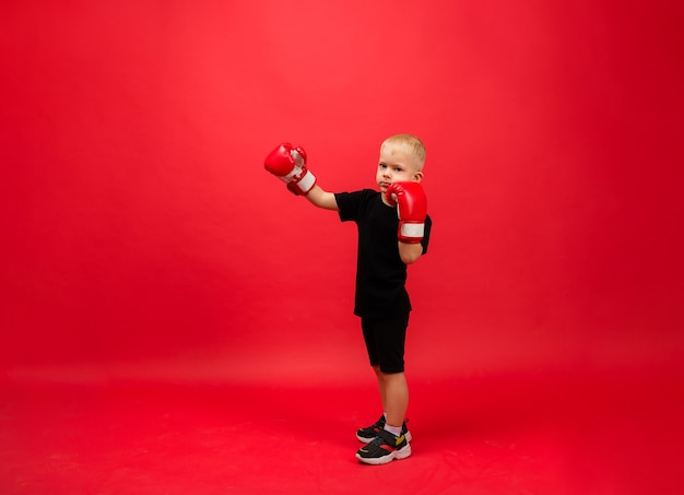 Toddler boy boxer in red boxing gloves stands sideways at full height and makes a punch on a red wall Premium Photo