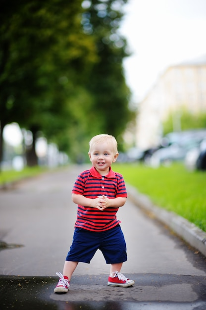 Toddler boy playing in the city at the spring or summer day Premium Photo