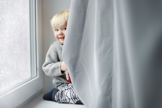 Toddler boy playing on the window sill at home Premium Photo