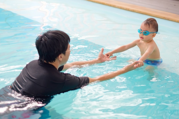 Toddler boy wear swimming goggles playing in indoor swimming pool with his father Premium Photo