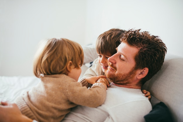 Toddler on father tummy at home Free Photo