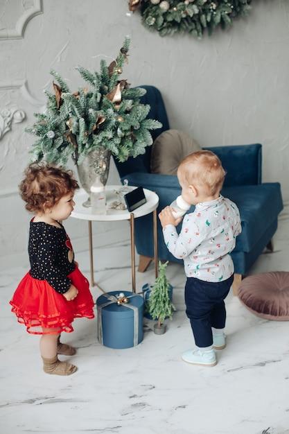Ragazza del bambino e ragazzo con una bottiglia in piedi da tavolo elegante con vaso di rami di abete. Foto Gratuite
