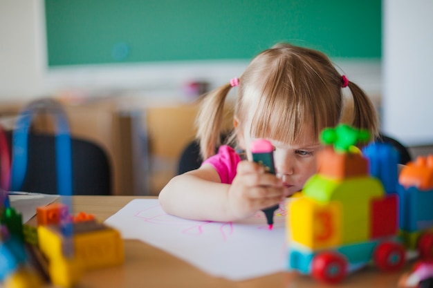 Toddler girl drawing on paper in classroom Free Photo