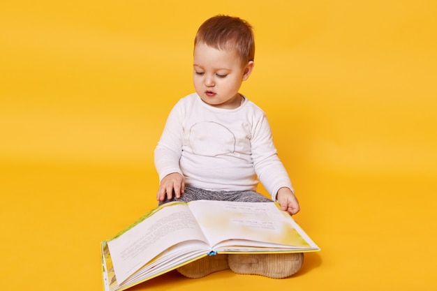 Toddler girl pretends to read book while sitting on floor, viewing pictures and turning pages, little girl looks concentrated Free Photo