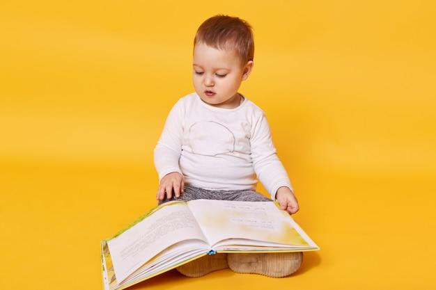 Малышка делает вид, что читает книгу, сидя на полу, просматривая картинки и перелистывая страницы, маленькая девочка выглядит сосредоточенно Бесплатные Фотографии