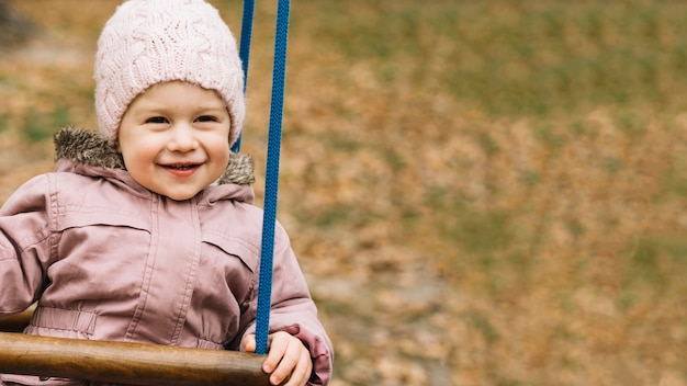 Toddler girl in warm clothes on swing in autumn park Free Photo