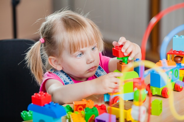 Toddler girl with colorful toys Free Photo