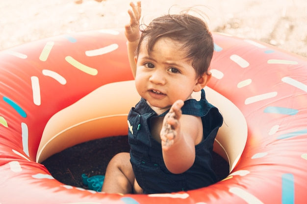 Toddler sitting in swimming circle Free Photo