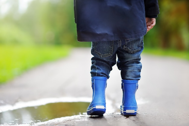 Toddler wearing rain boots standing near a puddle on the summer or autumn day Premium Photo