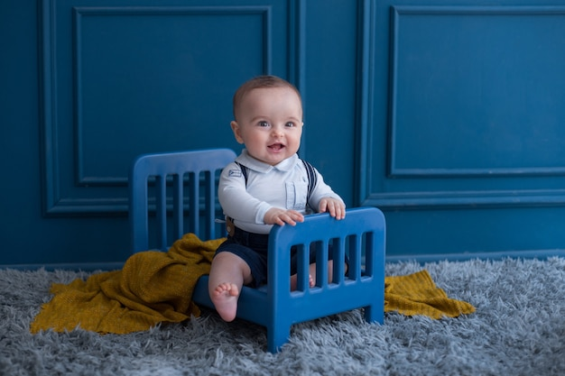 A toddler with elegant outfist inside decorative bed in the room. Free Photo