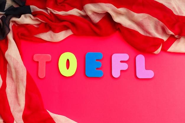 赤い背景の上の単語toeflとアメリカの国旗 Premium写真