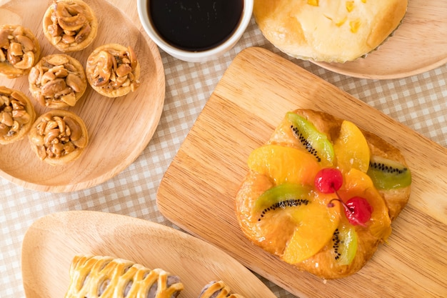 Toffee cake,bread with corn mayonaise, taro pies, danish mixed fruit with jam and coffee cup Free Photo