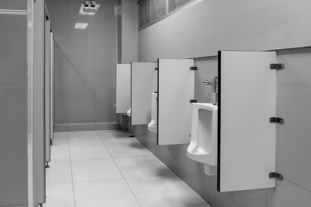 The toilet of man with toilet view by urinals at the old toilet in black and white tone in the office. Premium Photo