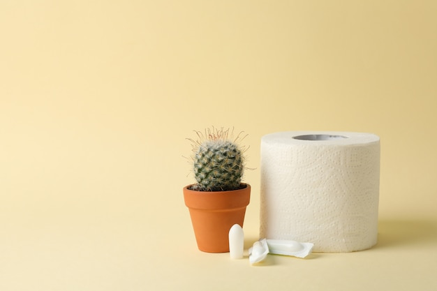 Toilet paper, candles and cactus on beige. hemorrhoids Premium Photo