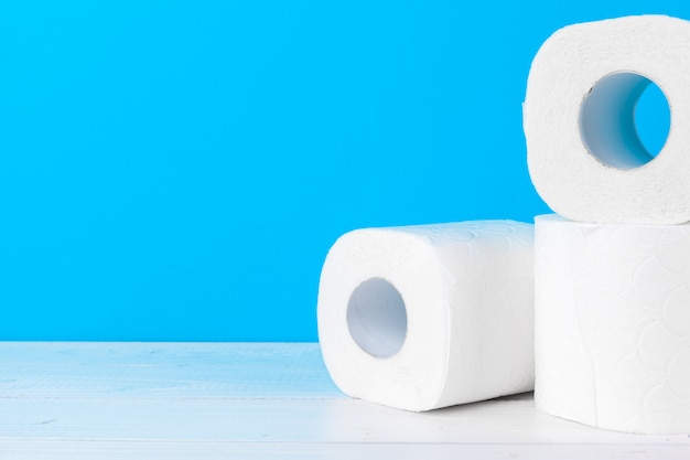 Toilet paper rolls stacked against blue Premium Photo