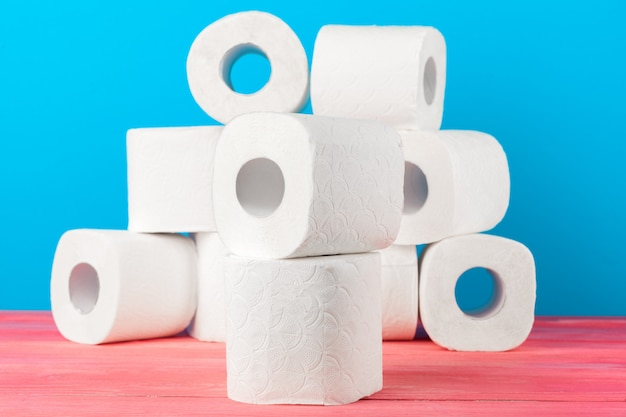 Toilet paper rolls stacked against blue Premium Photo