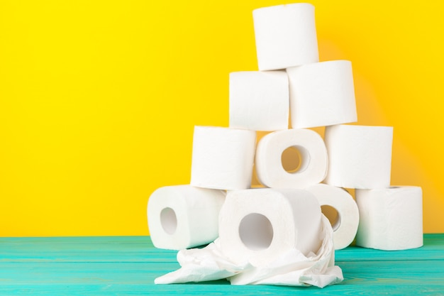 Toilet paper rolls stacked against yellow paper Premium Photo