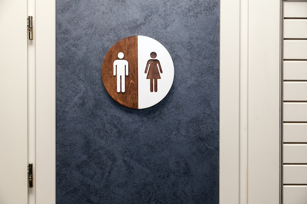 Toilet, wc icon, round wooden white and brown sign on restroom door in the hallway Premium Photo