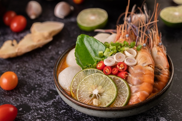 Tom yum kung in a bowl with tomato, chili, lemongrass, garlic, lemon, and kaffir lime leaves Free Photo
